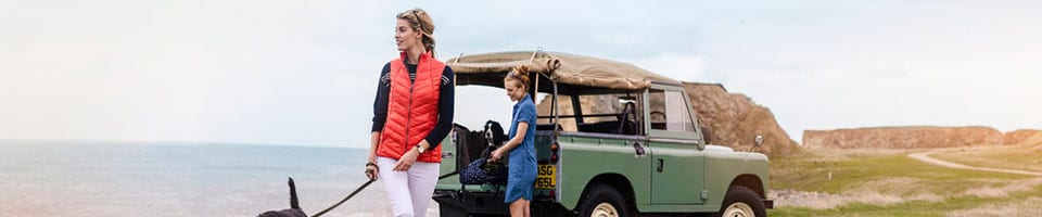 Women Wearing Country Style Clothing Standing With Dogs Next to Land Rover