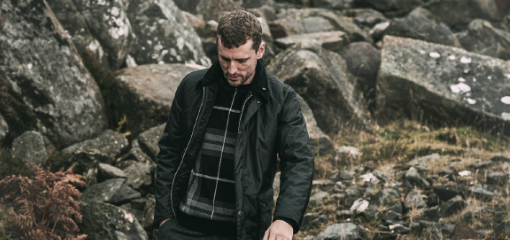 Man Trekking in Mountain Range Wearing Barbour Wax Jacket