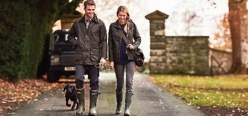 Couple wearing Barbour attirew alking down drive with dog on Country Estate