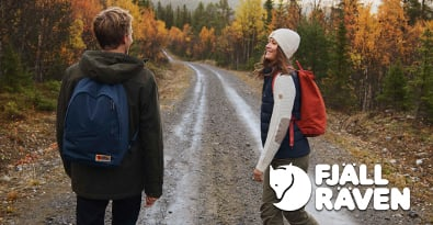 Couple on Forest Trail Wearing Fjällräven Jacket, Gilet, Hats, Trousers and Backpacks