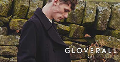Man Wearing Gloverall Dark Jacket Standing Next To Dry Stone Wall