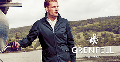 Man Wearing the Iconic Grenfell Jacket Standing by Lake and Rolling English Coutryside