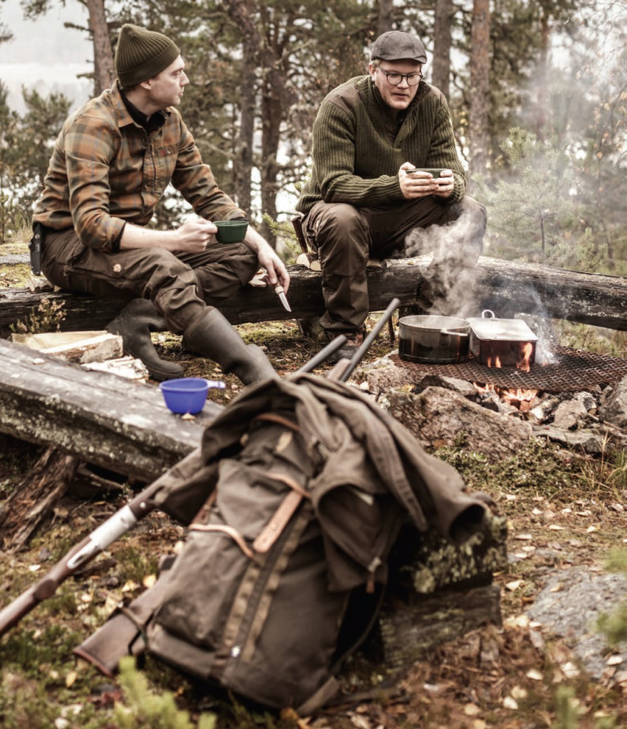 Hunters Sitting Round Campfire in Forrest