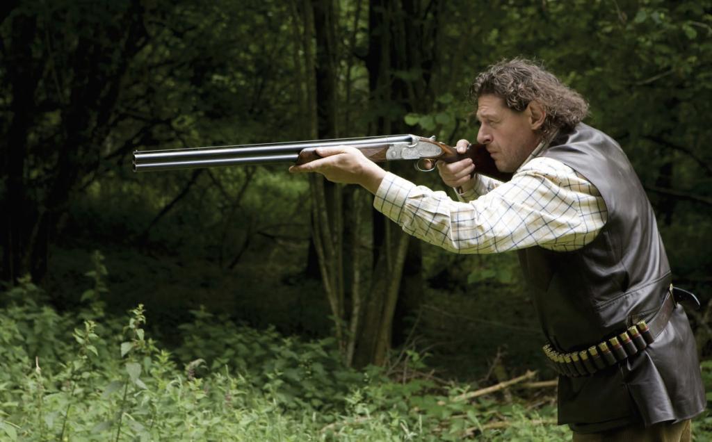 Marco Pierre White game shooting, wearing hunting jacket and cartridge belt