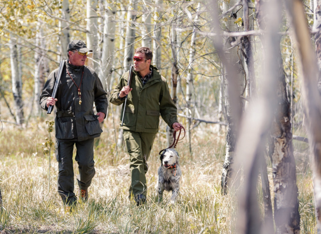 Two Hunters in Forest With Gun Dog