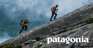 Climbers Wearing Patagonia Weatherproof Clothing and Backpacks Acscending Mountain