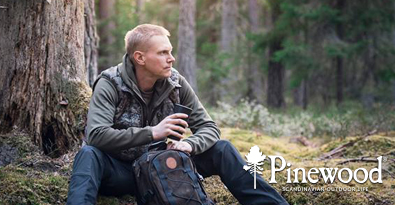 Man Sitting in forest wearing Pinewood clothing & hunting vest.