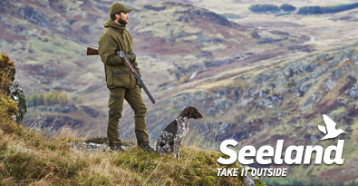 In the Wilderness Wearing Seeland Hunting Clothing, Jacket, Trousers With Shotgun and Working Dog