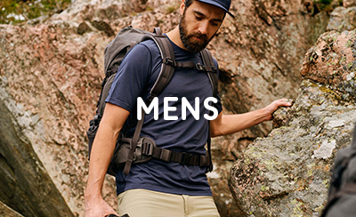 Man walking over rocky terrain with Fjallraven Backpack, wearing Cap and Navy Blue T-Shirt
