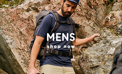 Man walking over rocky terrain with Fjallraven Backpack, wearing Cap and Navy Blue T-Shirt.