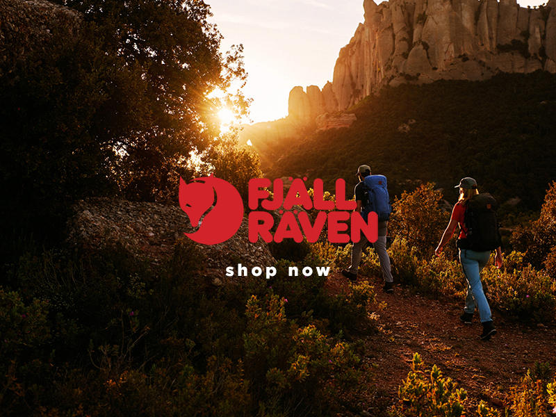 Trekking through a canyon at sunrise, two walkers wearing Fjallraven attire and Backpacks.