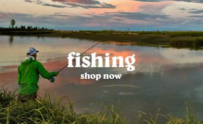 Man Fishing on Riverbank Wearing Green Waterproof Hooded Jacket and Patagonia Cap