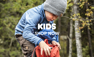 Toddler Wearing Fjallraven Kids Fleece, Vidda Trousers and Beanie Hat, Checking the contents of Fjallraven Raven Mini Backpack.
