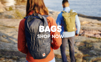 Man and Woman Walking Across Rocky Coastline Carrying Fjallraven Backpacks and Bags, Wearing Fjallraven Jackets and Clothing.