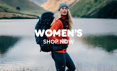 Woman Trekking through Mountain Fjord, carrying large Fjallraven Backpack, wearing Green Beanie Hat and High Coast Lite Jacket.