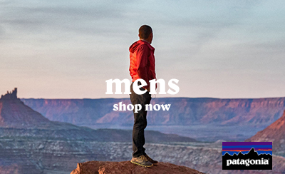 Man Wearing Orange Weatherproof Jacket, Trousers and Trainers standing on Rocky Peak in the Grand Canyon, Arizona, USA