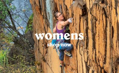 Woman Mountaineer solo climbing, ascending a rocky cliff face.