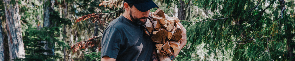 Man Wearing T-Shirt Collecting Wood in Forest