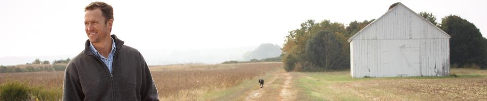 Man Wearing Weatherproof Fleece Jacket Standing on Farm Track With Working Dog