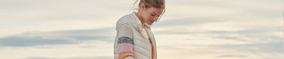 Woman Wearing White Quilted Gilet & Pastel Shade Knitwear Sweater