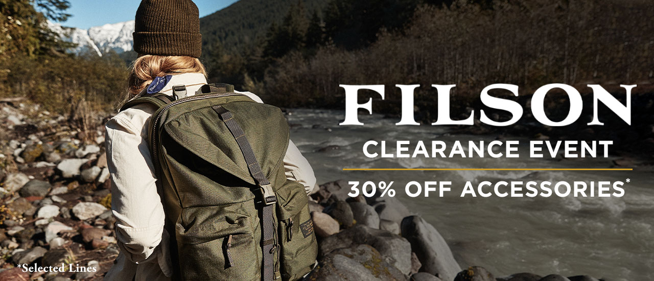 Woman wearing Filson ripstop backpack and wool knitted hat walking past Forest Stream