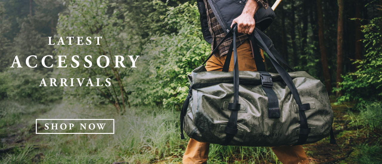 Man Carrying rugged Filson Duffle Bag through the forest