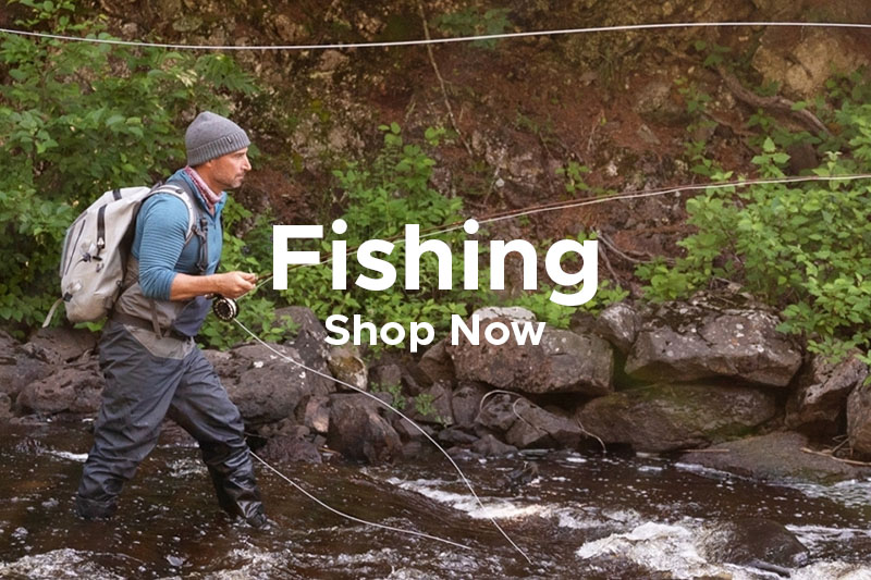 Man Fishing in River, Wearing Wading Pants, Vest, Beanie and Backpack.