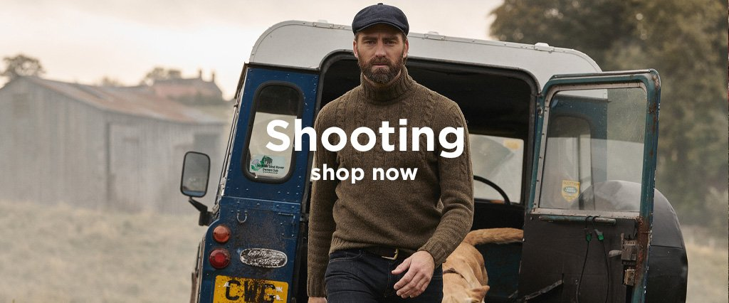 Country Gent out Shooting wearing Barbour Flat Cap and Woollen Jumper with hunting Dog and Land Rover.