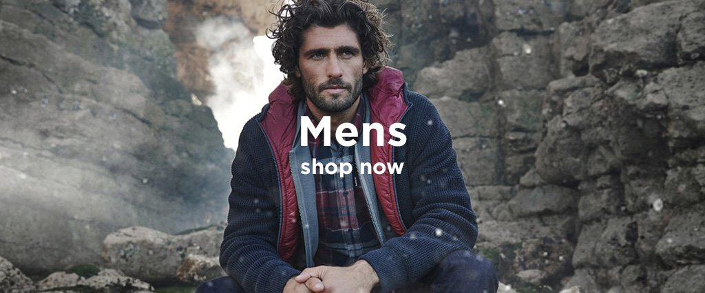 Man wearing Navy Barbour jacket with red lining crouching by stone ruin.