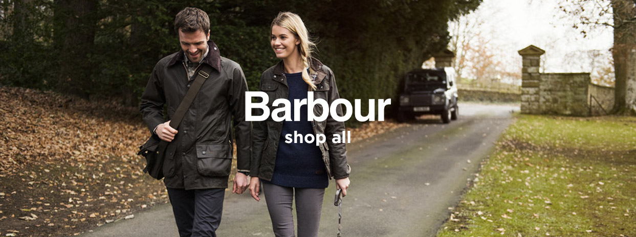 Man and Woman wearing Barbour Wax Jackets walking down drive of Country Estate