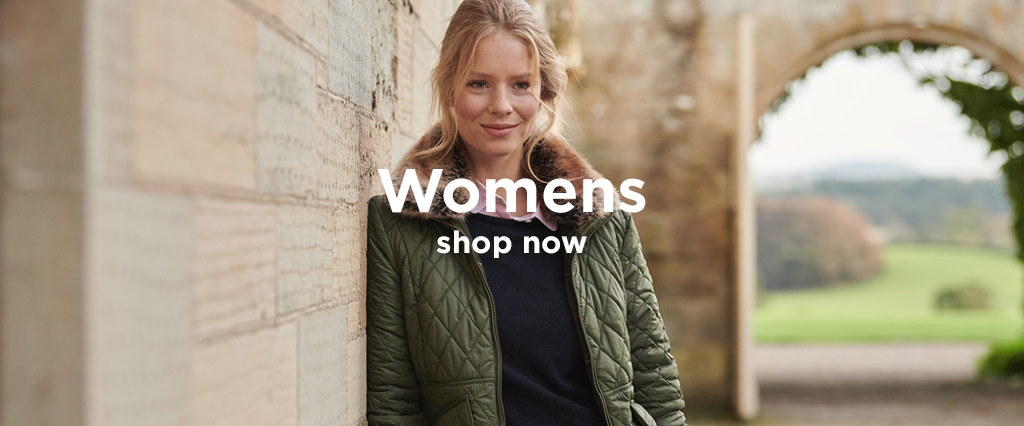 Woman wearing Barbour Olive Green Hawthorns Quilted Jacket standing by country buildings.
