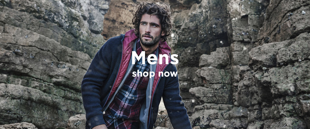 Man wearing Barbour Fleece Jacket and Country Check Shirt Standing In Front of Rock Face.