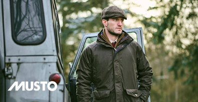 Country Gent Wearing Musto Jacket & Tweed Cap Standing next to Land Rover