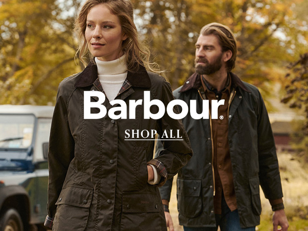 Man and Woman wearing Barbour Jackets and Country attire walking past Land Rover