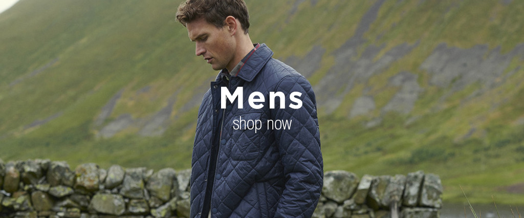 Man Wearing Navy Barbour Heritage Quilt Jacket next to dry stone wall.