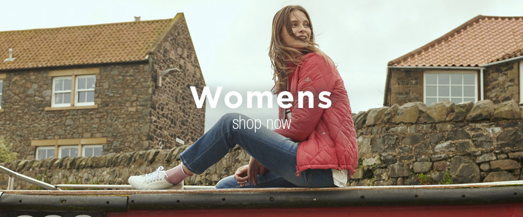 Sitting Woman Wearing Barbour Quilt Jacket and Slim Fit Blue Jeans.