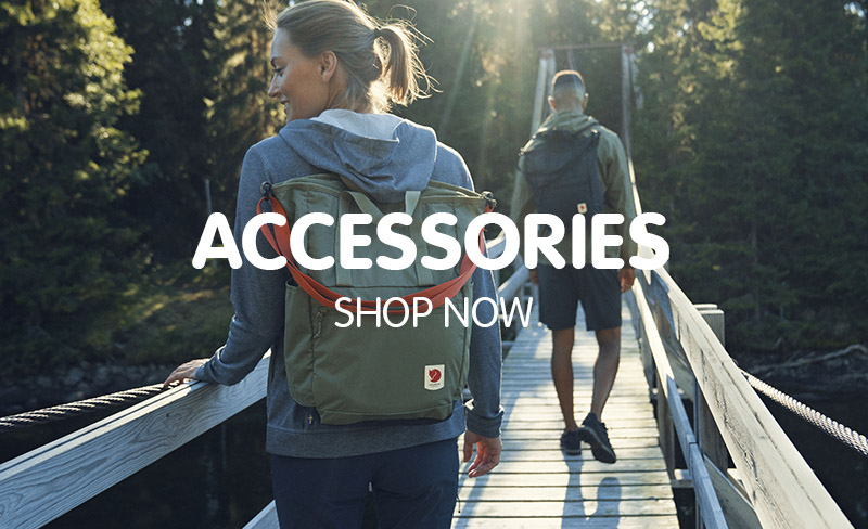 Man and Woman Crossing Wooden Footbridge with Fjallraven Backpacks.