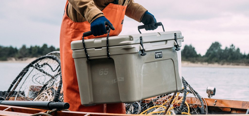Fisherman Carrying Yeti Tundra 65 Cooler Standing in Boat on Lake